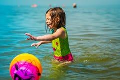 La niña consigue mojada después de jugar una bola en el mar Fotos de archivo
