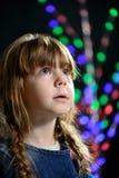 La niña contra un fondo oscuro mira a un lado Fotografía de archivo libre de regalías