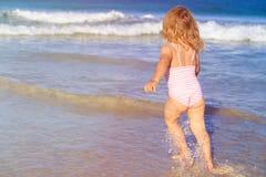 La niña corre el juego con las ondas en la playa Foto de archivo