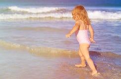 La niña corre el juego con las ondas en la playa Imagen de archivo libre de regalías