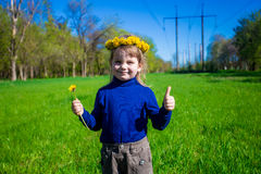 La niña corre en la hierba verde con un paquete de flores y de pulgar para arriba foto de archivo libre de regalías