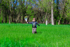 La niña corre a lo largo de la hierba verde con las flores Fotografía de archivo libre de regalías