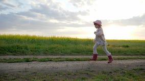La niña corre a lo largo del camino del campo, niño corriente, niño feliz que se divierte fuera de la ciudad, niñez sana, limpia metrajes