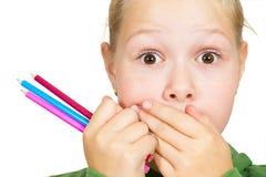 La niña cubre su boca con sus manos Fotos de archivo