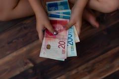 La niña cuenta el dinero, 100, 200 shekels Imagen de archivo libre de regalías