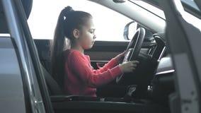 La niña da vuelta a la rueda stearing almacen de video