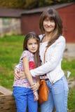La niña de Beautifal y la madre feliz en el otoño parquean imagen de archivo libre de regalías