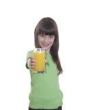 La niña de la sonrisa con el zumo de naranja Foto de archivo