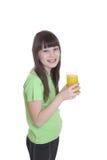 La niña de la sonrisa con el zumo de naranja Imagen de archivo