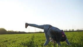 La niña de pelo largo en la ropa blanca está jugando al aire libre Ella hace volteretas Un prado verde grande Diversión y almacen de video