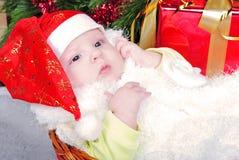 La niña debajo del árbol de navidad en el casquillo del Año Nuevo Fotos de archivo