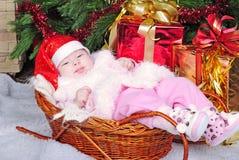 La niña debajo del árbol de navidad en el casquillo del Año Nuevo Fotografía de archivo libre de regalías