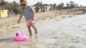 La ni?a deja una nadada del flamenco del rosa del juguete en el mar almacen de video