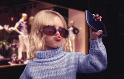 La niña del encanto habla en el teléfono Fotos de archivo libres de regalías