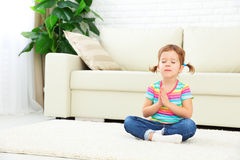La niña del niño medita en la posición de loto y practica yoga Fotografía de archivo