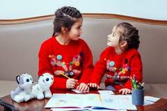 La niña del pensil de la Navidad del Año Nuevo escribe a letra Papá Noel el sofá rojo de la tabla del niño de la pluma del juguet foto de archivo libre de regalías