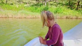 La niña del primer defiende en barco del pedal del agua el banco cercano metrajes