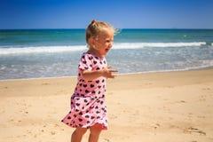 La niña del primer en rosa llora con alegría por la resaca de la onda Imagen de archivo libre de regalías