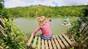 La niña del primer se sienta en banco en el lago acortado watches de Bush metrajes