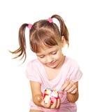 La niña desempaqueta la pequeña caja de regalo Imagen de archivo libre de regalías