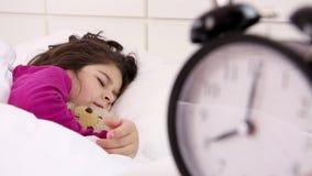 La niña despierta, ascendente cercano del despertador almacen de metraje de vídeo
