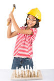 La niña destruye el juego de ajedrez con el martillo I Fotos de archivo