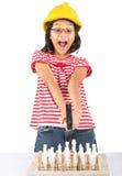 La niña destruye el juego de ajedrez con el martillo II Foto de archivo libre de regalías