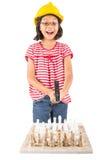 La niña destruye el juego de ajedrez con el martillo IV Foto de archivo libre de regalías
