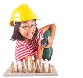 La niña destruye el juego de ajedrez con el taladro II Imagen de archivo libre de regalías