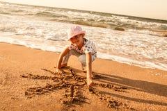 La niña dibuja el sol en la arena en la playa Fotos de archivo libres de regalías