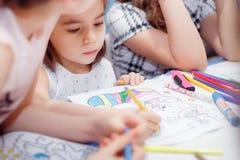 La niña dibuja sentarse en la tabla en sitio Foto de archivo