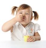 La niña divertida come el yogur Fotografía de archivo
