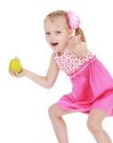 La niña divertida con una manzana en su mano muestra Imágenes de archivo libres de regalías