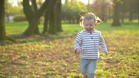 La niña divertida está corriendo lejos de su madre que juega al aire libre en el parque Niño femenino activo que se divierte dura almacen de metraje de vídeo