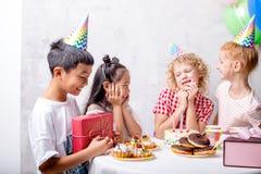 La niña divertida está esperando los regalos para su cumpleaños fotografía de archivo