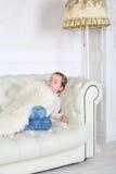 La niña duerme debajo de la piel blanca en el sofá blanco Foto de archivo