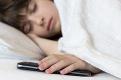 La niña duerme en la cama que sostiene su teléfono móvil Problema de fotos de archivo