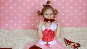 La niña dulce en gafas de sol rojas en la forma de corazones envía besos del aire El niño divertido envía beso Fondo rosado metrajes