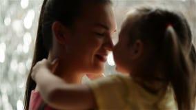 La niña dulce es de abrazo y que besa a su mamá joven hermosa Día de madres feliz La cascada está en fondo almacen de metraje de vídeo