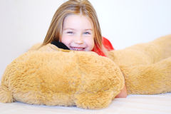 La niña dulce está abrazando un oso de peluche mientras que miente en su cama Imagen de archivo