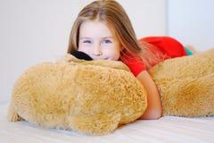 La niña dulce está abrazando un oso de peluche mientras que miente en su cama Fotografía de archivo libre de regalías