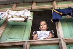 La niña dulce mira fijamente abajo de su ventana de madera de la casa con ropa de la ejecución en la parte superior imagenes de archivo