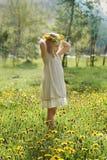 La niña el hierba verde y verano florece al aire libre Imagen de archivo libre de regalías
