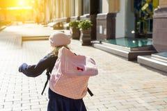 La niña elegante con una mochila, en una capa y la boina francesa corren a la escuela imagenes de archivo