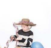 la niña elegante concentró en el adornamiento de su sombrero de moda con las cintas Imágenes de archivo libres de regalías