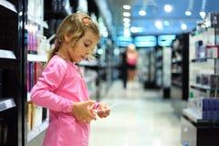 La niña elige perfume en departamento del perfume fotos de archivo