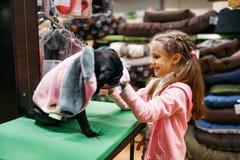 La niña elige la ropa para el perrito en la tienda de animales Imagen de archivo