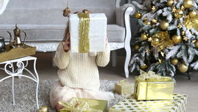 La niña emocional sacude una caja de regalo cerca del árbol de navidad en casa almacen de video