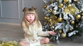 La niña emocional se sienta debajo del árbol de navidad y sopla un confeti de las manos metrajes