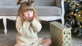 La niña emocional sopla un confeti de las manos cerca del árbol de navidad en casa almacen de metraje de vídeo